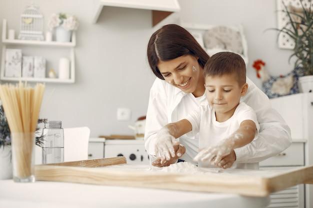 Familie sitzt in einer küche und kocht den teig für kekse Kostenlose Fotos