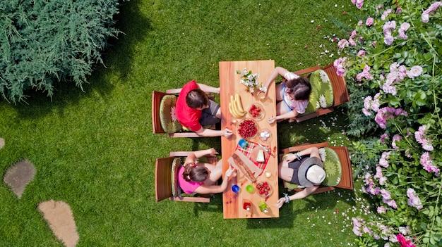 Familie und freunde, die zusammen draußen auf sommergartenparty essen. luftaufnahme des tisches mit essen und getränken von oben. freizeit-, ferien- und picknickkonzept Premium Fotos