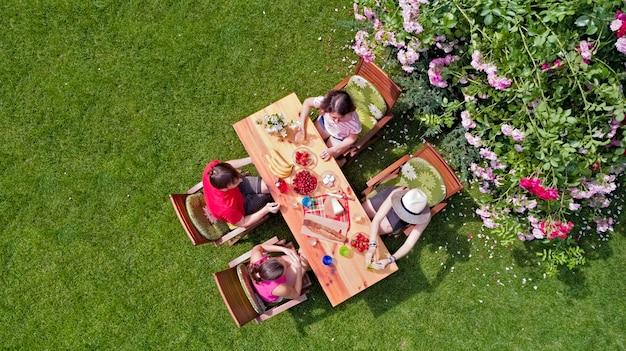 Familie und freunde essen zusammen im freien auf sommergartenparty. luftaufnahme des tisches mit essen und getränken von oben. freizeit-, ferien- und picknickkonzept Premium Fotos