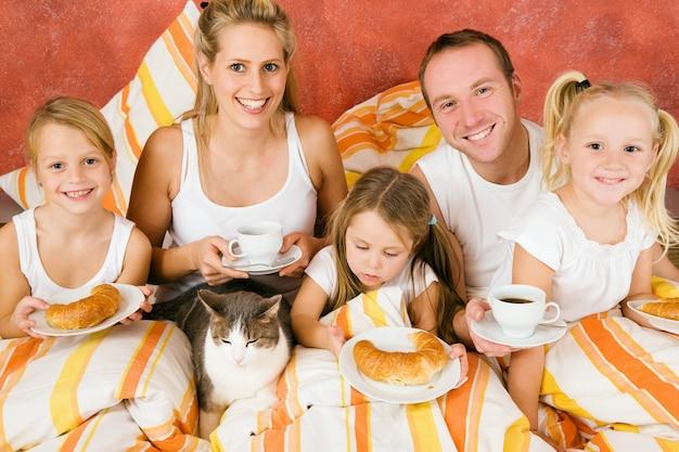 Familie und katze, die im bett frühstücken Premium Fotos