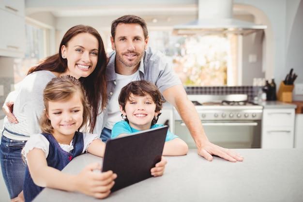 Familie unter verwendung der digitalen tablette bei bei tisch stehen Premium Fotos