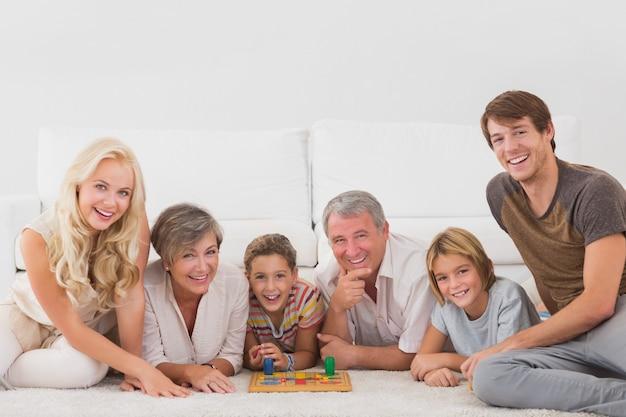 Familie, welche die kamera mit brettspielen betrachtet Premium Fotos