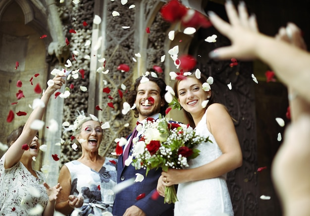 Familie wirft rosenblätter an der frisch vermählten braut und am bräutigam Premium Fotos