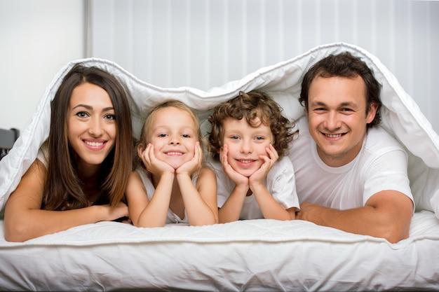 Familien mit kindern im bett unter einer decke. Premium Fotos