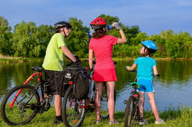Familienfahrrad fahren im freien, aktive eltern und kind radfahren und entspannen in der nähe von schönen fluss Premium Fotos