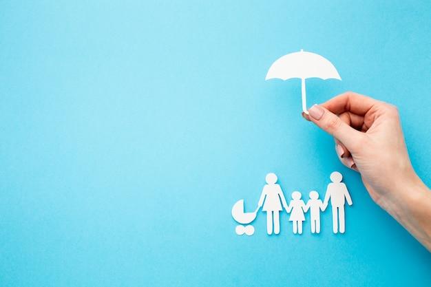 Familienfigur und hand, die regenschirmform hält Kostenlose Fotos