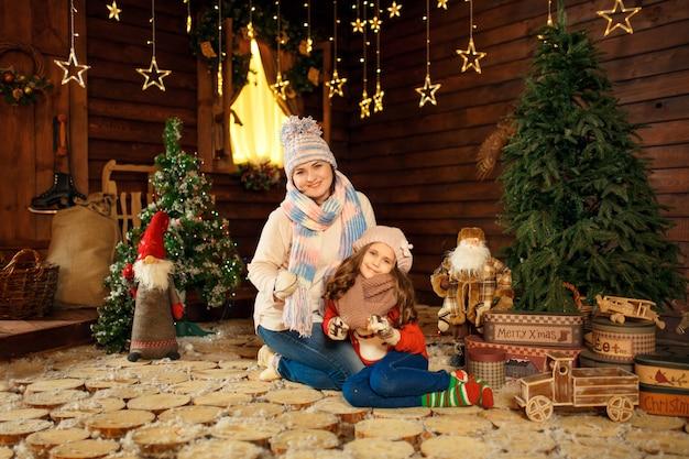 Familienfoto der mutter und der tochter, die auf den boden mit nettem kaninchen legen. weihnachtsdekoration Premium Fotos