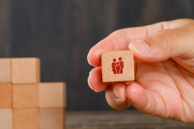 Familienkonzept auf holztischseitenansicht. hand hält holzwürfel. Kostenlose Fotos