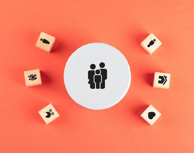Familienkonzept mit ikonen auf holzwürfeln auf roter tischflachlage. Kostenlose Fotos
