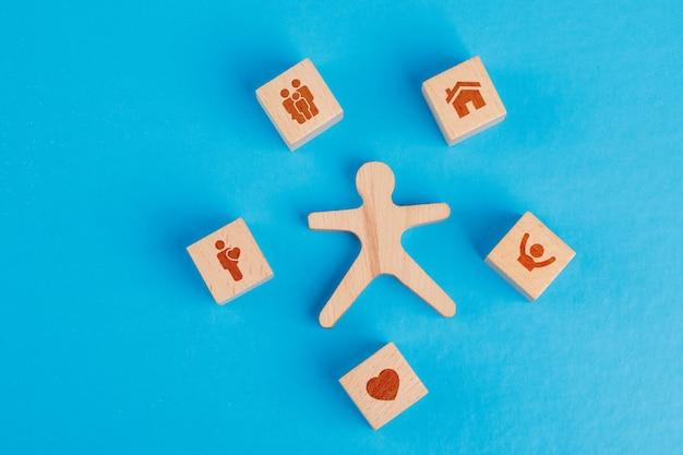 Familienkonzept mit ikonen auf holzwürfeln, menschliche figur auf blauem tisch flach legen. Kostenlose Fotos