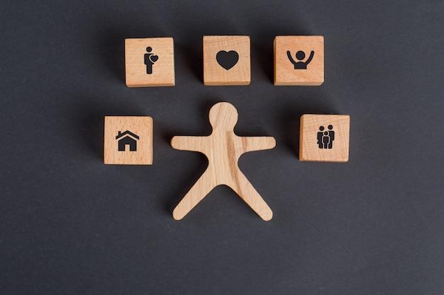 Familienkonzept mit ikonen auf holzwürfeln, menschliche figur auf dunkelgrauer tischflachlage. Kostenlose Fotos