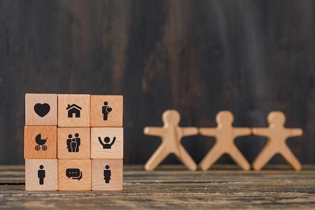 Familienkonzept mit ikonen auf holzwürfeln, menschliche figuren auf holztischseitenansicht. Kostenlose Fotos