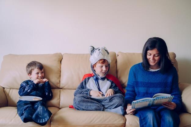 Familienlebensstil drinnen. junge mutter liest ihren kindern in karnevalskostümen ein interessantes buch vor. geschichtenerzähler mit mama. kinder ohne schule verbringen ihre zeit drinnen zu hause. Premium Fotos