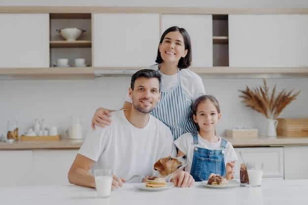 Familienporträt der glücklichen mutter, der tochter und des vaters werfen an der küche während der frühstückszeit auf, essen köstliche selbst gemachte pfannkuchen, ihr hund wirft nahe auf, haben freundliche gute verhältnisse, lieben sich Premium Fotos