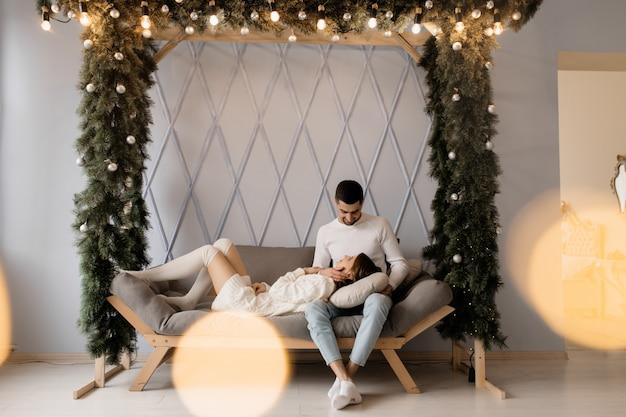 Familienporträt. mann und frau entspannen sich auf weichem grauem schlechtem in einem raum mit weihnachtsbaum Kostenlose Fotos