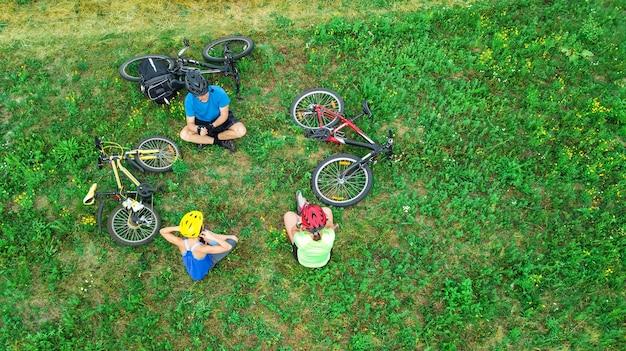 Familienradfahren auf fahrrädern im freien luftaufnahme von oben, glückliche aktive eltern mit kind haben spaß und entspannen auf gras Premium Fotos