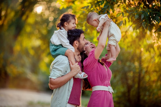 Familientag! glückliche eltern mama und papa halten ihren sohn und ihre tochter in den armen ihrer kleinen kinder. sie lachen und haben spaß im sommer bei einem spaziergang im park Premium Fotos