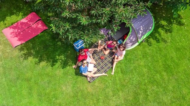 Familienurlaub auf dem campingplatz luftaufnahme von oben, eltern und kinder entspannen sich und haben spaß im park, zelt und campingausrüstung unter baum, familie im camp im freien konzept Premium Fotos