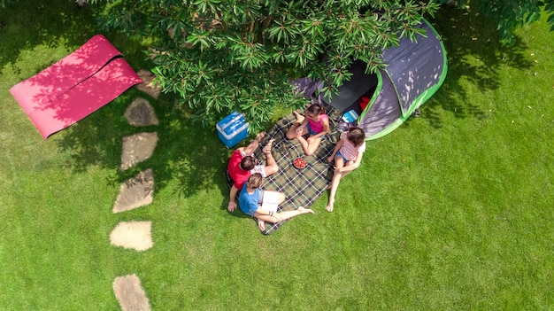 Familienurlaub in der luftaufnahme des campingplatzes von oben, eltern und kinder entspannen sich und haben spaß in park-, zelt- und campingausrüstung unter baum, familie im camp im freien konzept Premium Fotos