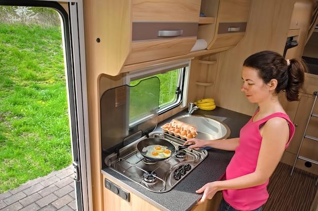 Familienurlaub, rv-urlaubsreise, camping, glücklich lächelnde frau, die im wohnmobil kocht, wohnmobilinnenraum Premium Fotos