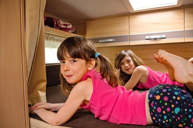 Familienurlaub, rv-urlaubsreise, camping, glücklich lächelnde kinder reisen auf wohnmobil, kinder im wohnmobil-innenraum Premium Fotos