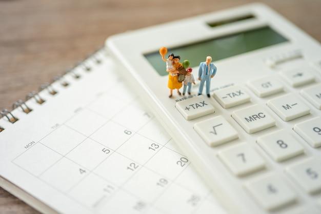Family miniature people pay queue jährliches einkommen (tax) für das jahr auf dem taschenrechner. Premium Fotos
