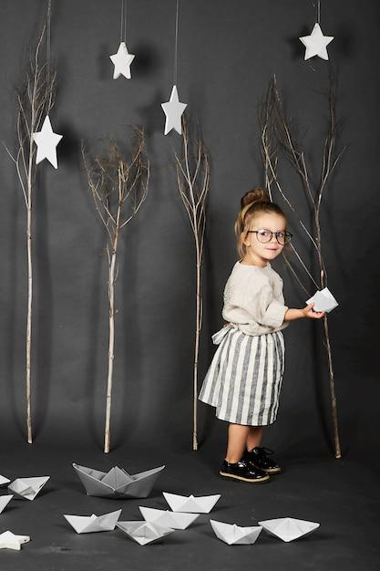 Fanny kleines mädchen mit brille auf grauem hintergrund mit sternen, bäumen und papierbooten Premium Fotos