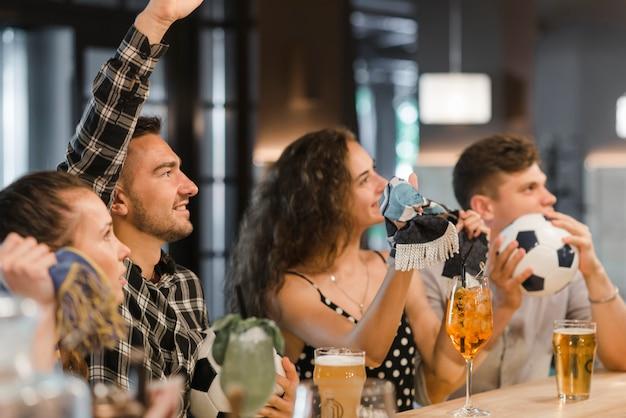 Fans beobachten fußballspiel im fernsehen in der bar Kostenlose Fotos