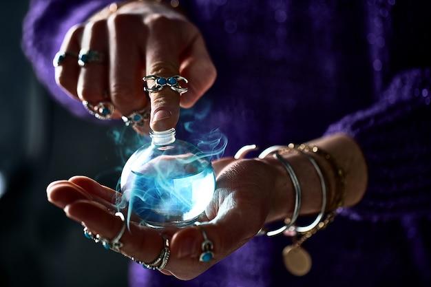 Fantasiehexenzaubererfrau, die bezaubernde magische elixiertrankflasche für liebeszauber, hexerei und wahrsagerei verwendet. magische illustration und alchemie Premium Fotos