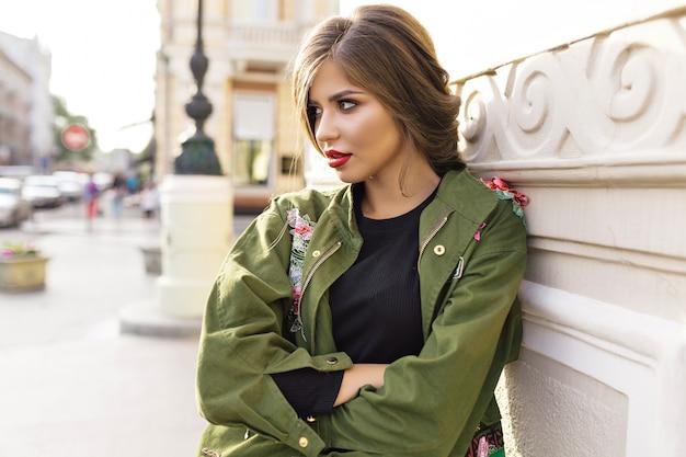 Fantastische brünette mit stilvoller frisur und roten lippen, die auf der straße posieren Kostenlose Fotos