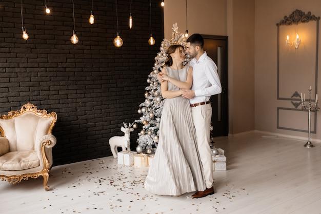 Fantastischer gekleideter mann und frau im silbernen kleid umarmen sich zarte stellung vor einem weihnachtsbaum Kostenlose Fotos