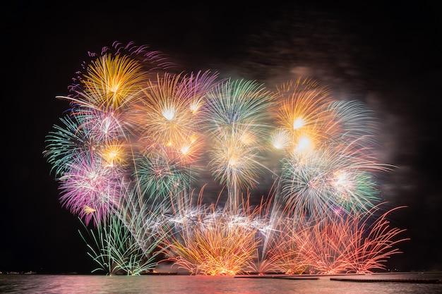 Fantastisches multicolor-feuerwerk, das für die feier vom großen boot über dem meer explodiert Premium Fotos