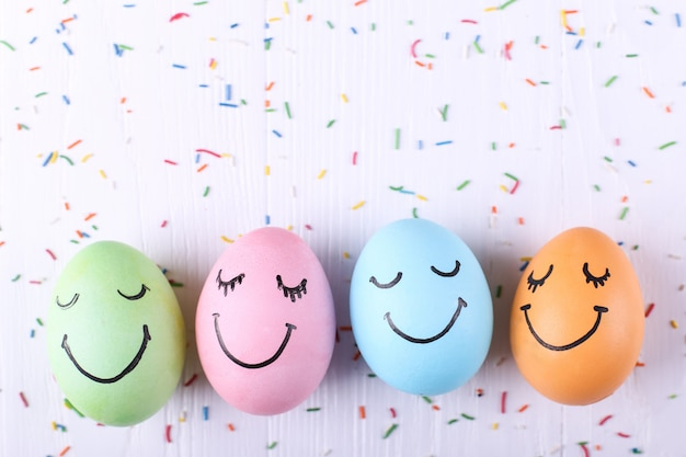 Farbige eier mit gemaltem lächeln glückliche ostern-grußkarte. Premium Fotos