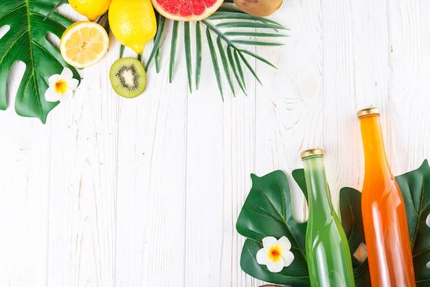 Farbige flaschen mit getränken und verschiedenen früchten Kostenlose Fotos