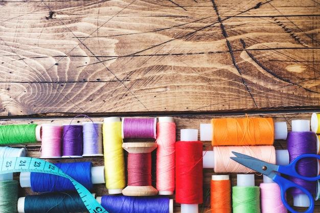 Farbige garnrollen ausgebreitet in reihen auf hölzernem hintergrund. platz kopieren. Premium Fotos