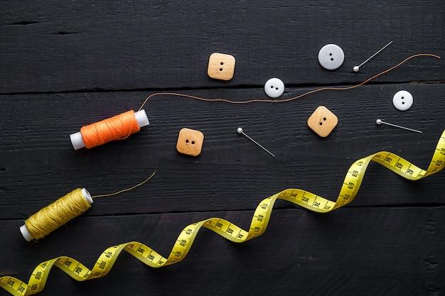 Farbige garnrollen, stifte, maßband und knöpfe zum nähen auf einer braunen holzoberfläche Premium Fotos