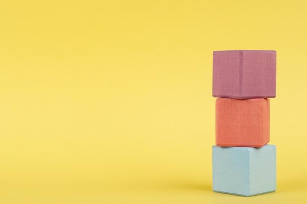 Farbige hölzerne würfel auf gelbem hintergrund, kinderbildung Premium Fotos