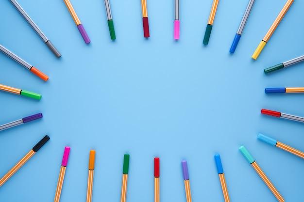 Farbige markierungen, die einen kreis mit kopierraum in der mitte auf einem blauen hintergrund bilden. zurück in die schule, design, kreativitätskonzept und handwerk. Premium Fotos