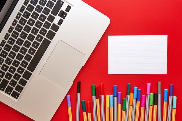 Farbige markierungen, laptop und ein leeres blatt papier, um auf einem roten hintergrund zu schreiben. konzept von design und kreativität. Premium Fotos