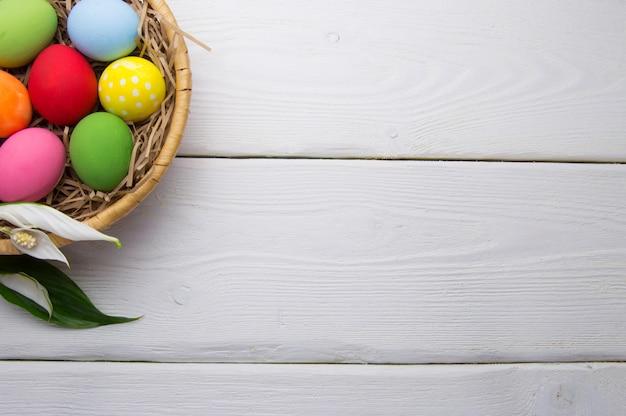 Farbige ostereier auf nestbeasket mit blume auf weißem holzoberflächenspitzenweiß Premium Fotos