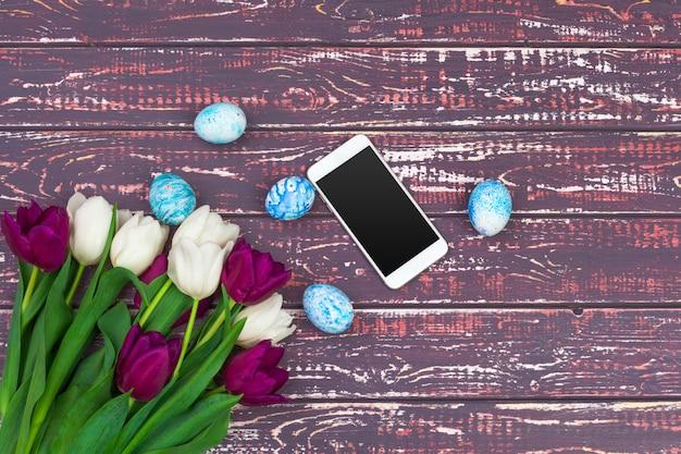 Farbige ostereier, tulpenblumen und smartphone Premium Fotos