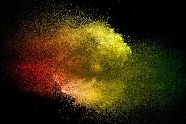 Farbige staubspritzenwolke auf dunklem hintergrund. gestartete bunte partikel im hintergrund. Premium Fotos