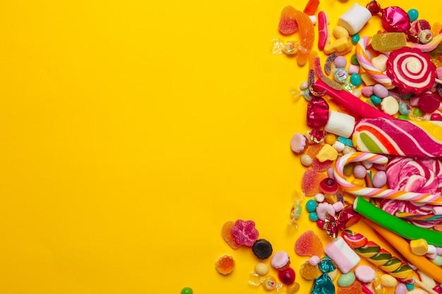 Farbige süßigkeiten auf gelbem hintergrund mit copyspace Premium Fotos