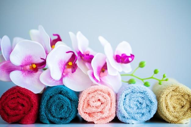Farbige tücher und orchidee auf weißer tabelle mit kopienraum auf badezimmer Premium Fotos