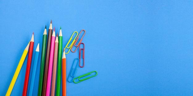 Farbige zeichenstiftbleistifte und -clips auf blauem hintergrund. Premium Fotos