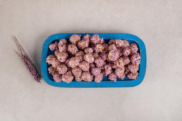 Farbiger weizenhalm neben einer holzplatte mit kandiertem popcorn auf marmor. Kostenlose Fotos