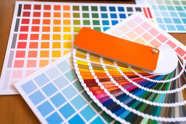 Farbmuster von den grafikdesignern, die auf schreibtischtabelle sich setzen. Premium Fotos