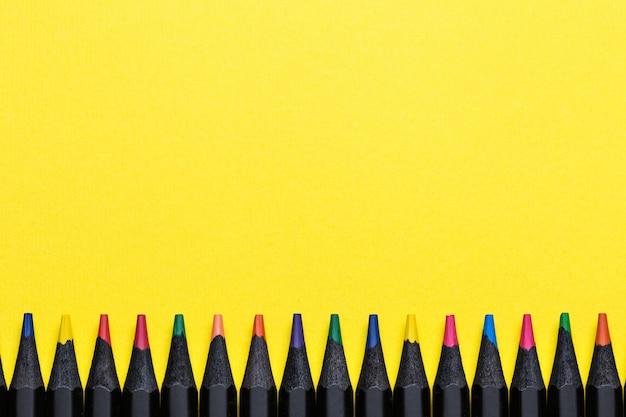 Farbstifte in einer reihe auf gelb Premium Fotos