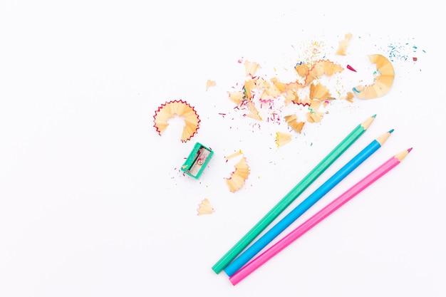 Farbstifte und bleistiftspitzer auf weißem hintergrund Premium Fotos