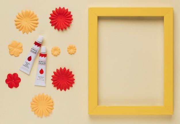 Farbtube; blumenausschnitt und gelbe holzrahmengrenze auf beige hintergrund Kostenlose Fotos